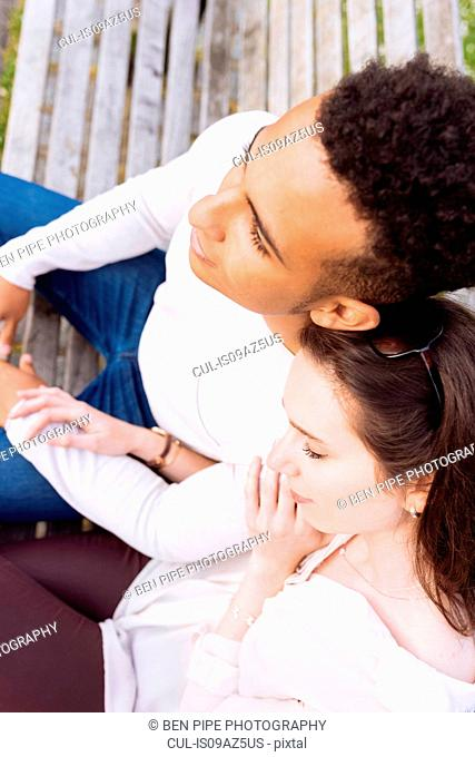High angle view of young couple sitting on park bench