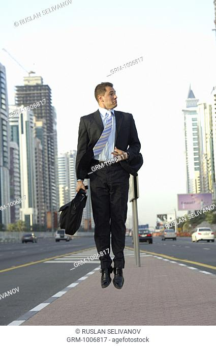 Businessman jumping in the air on Shaikh Zayed Road in Dubai