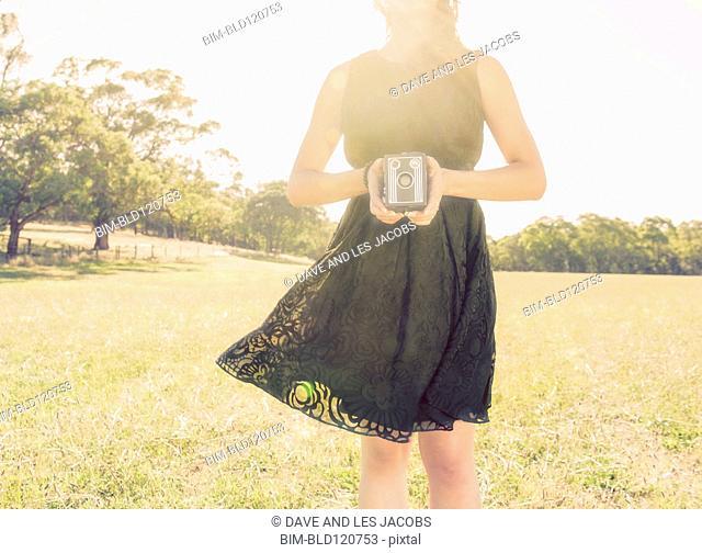 Hispanic woman holding vintage camera