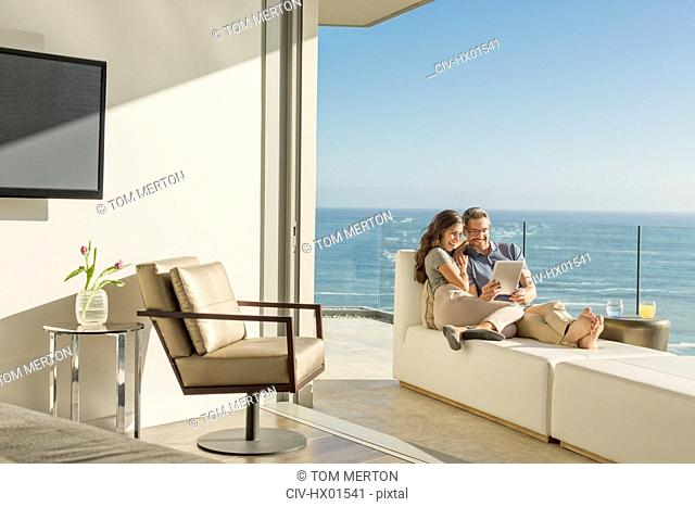 Couple using digital tablet on chaise lounge on sunny luxury balcony with ocean view