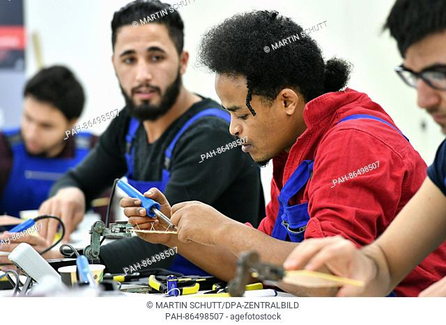 The refugge Henok Jared (R) from Eritrea is concentrated on his work on a circuit board at the educational workshop of the German Railway AG in Erfurt, Germany
