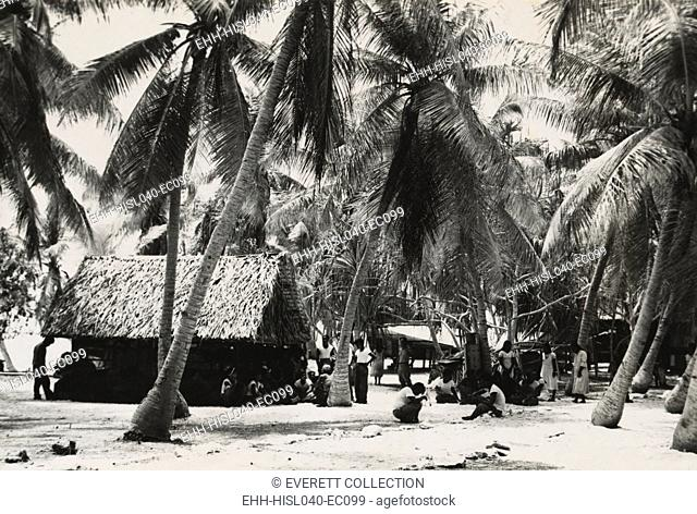 Bikini Islanders near thatched roof building shaded by palm trees, ca. March 1946. 167 islanders from 40 families were required to move to Rongerik Atoll by U
