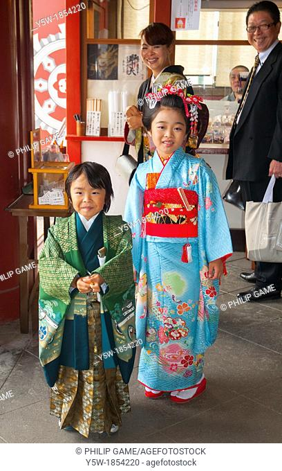 Japanese family visiting a temple in Ueno Park, Tokyo, the mother and children wearing traditional kimono dress