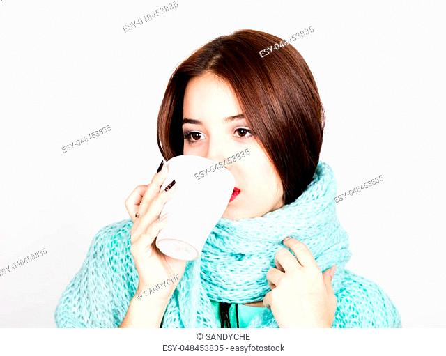 close-up portrait of a beautiful woman in a woolen scarf, drinking hot tea or coffee from a white cup