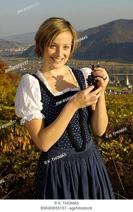 Wachau, young woman in traditional cloth, Blaudruckdirndl, with grapes, Austria, Lower Austria, Wachau, Weissenkirchen