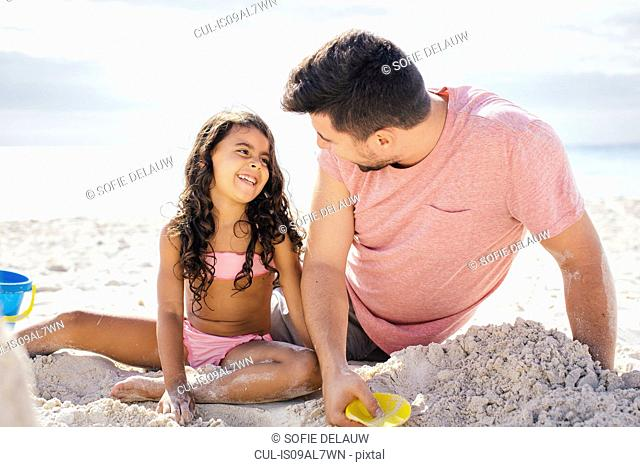 Girl and father building sandcastle on beach, Tuscany, Italy