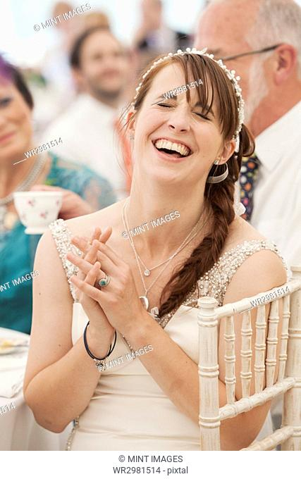 Bride in her wedding dress sitting in a marquee, hands clasped and laughing