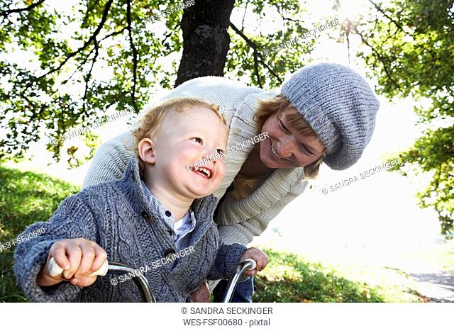 Happy mother with son on tricycle in the nature