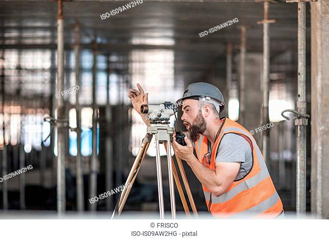 Young male surveyor looking through theodolite giving hand signal on construction site