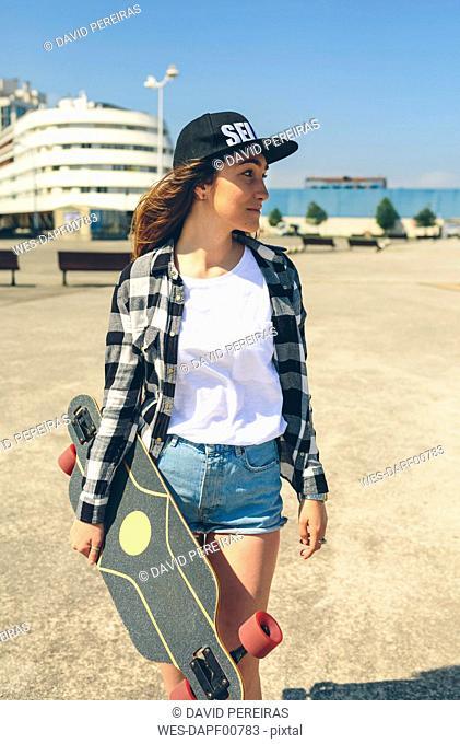 Young woman with longboard on beach promenade