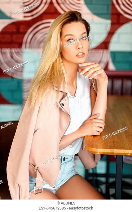 Blond young American woman in a fashion pink jacket and shorts is sitting on a chair at a table in a cafe