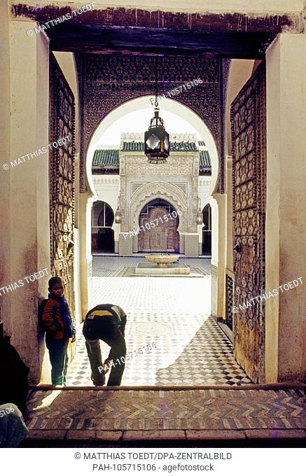 Believing Muslims take off their shoes before entering the Kairaouine Mosque in the Moroccan city of Fes, analogue undated photograph from March 1985