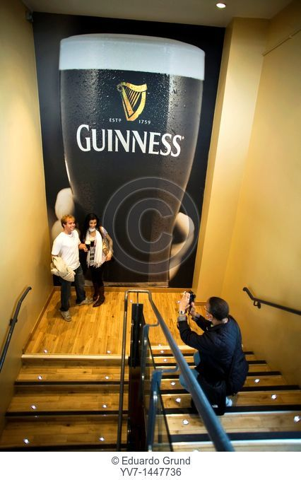Taking a photograph at a couple of tourists before a paint, in the stairs to access at the Gravity Bar in the Guinness Storehouse  Dublin, Leinster, Ireland
