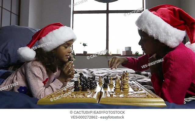 Kids in santa hats playing chess and thinking