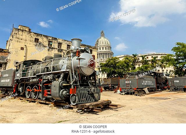 A vintage steam train in a restoration yard with the dome of the former Parliament Building in the background, Havana, Cuba, West Indies, Caribbean