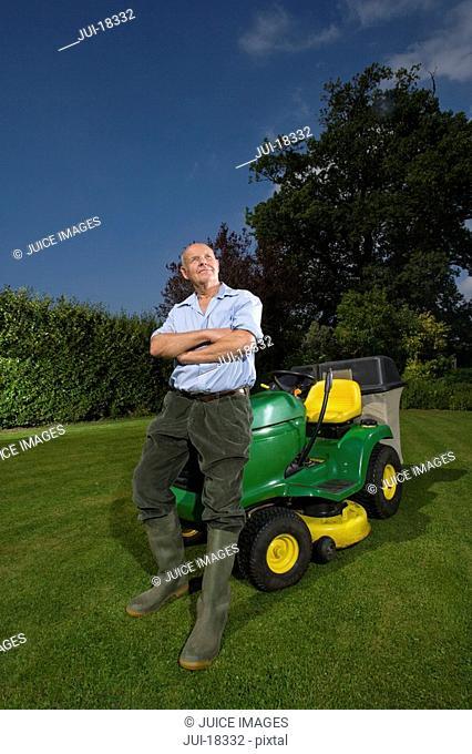Senior man leaning on riding lawn mower