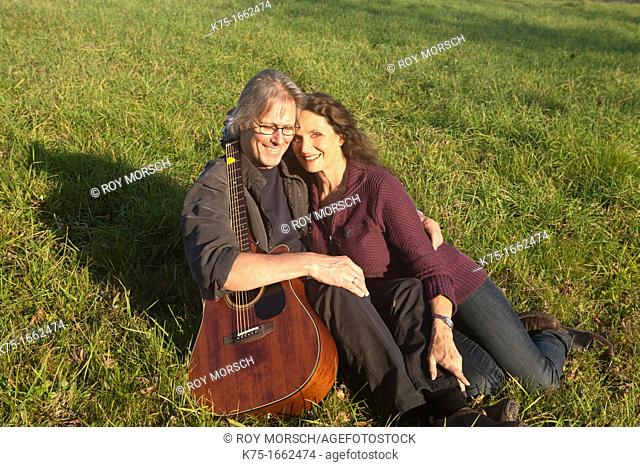 Couple with guitar sitting on lawn