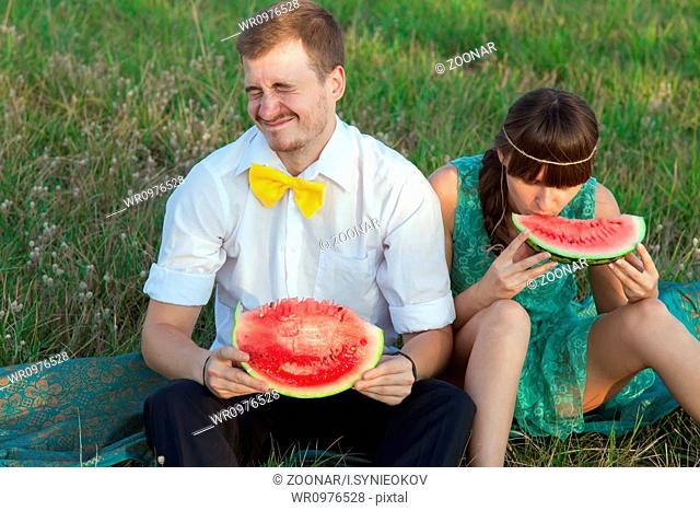 Young couple eating watermelon