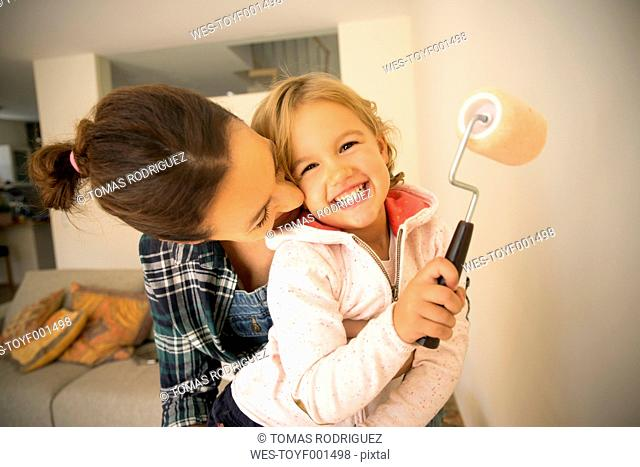 Happy woman with daughter painting a wall