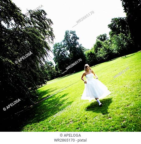 Happy bride running on field against trees