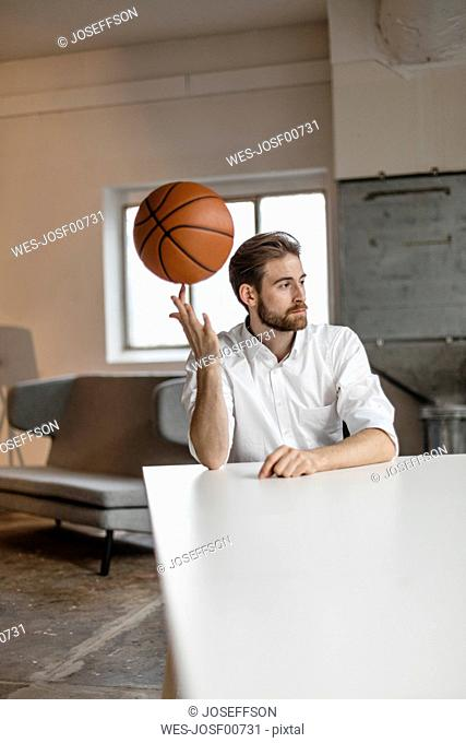 Portrait of pensive young businessman sitting at table in a loft balancing basketball on his finger