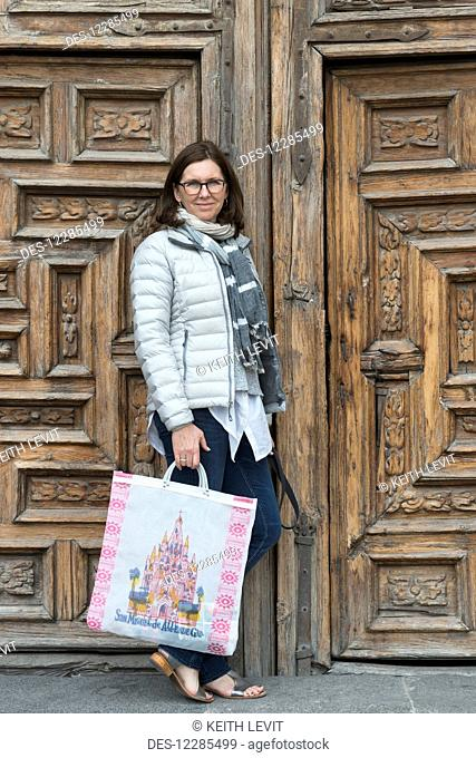A woman standing with a shopping bag outside ornate wooden doors; San Miguel de Allende, Guanajuato, Mexico