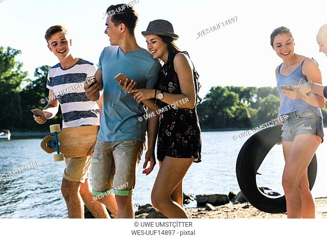 Group of happy friends with cell phones walking at the riverside