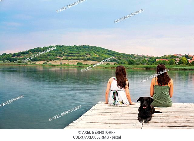 Women sitting with dog on pier