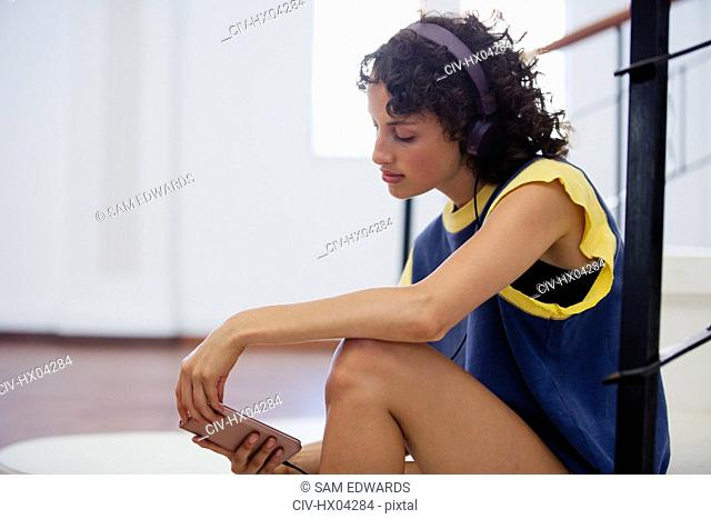 Young female dancer listening to music with headphones and mp3 player in dance studio