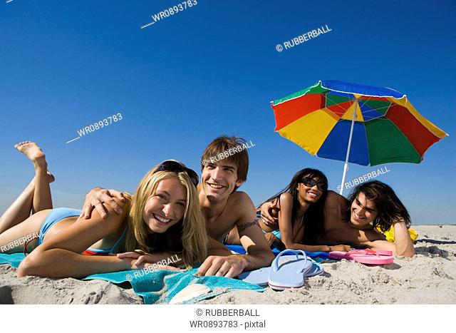 Portrait of four young people lying on the beach