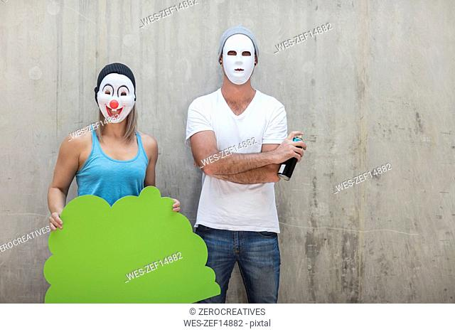 Man and woman wearing masks standing next to a concrete wall