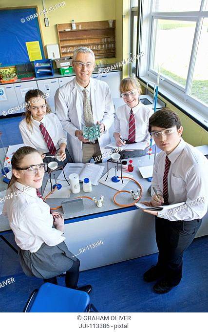 Portrait confident chemistry teacher and high school students conducting scientific experiment