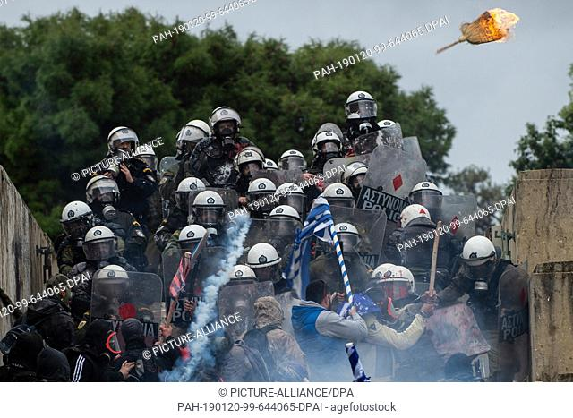 dpatop - 20 January 2019, Greece, Athen: A burning straw broom flies towards riot police during clashes with participants in a demonstration against the planned...