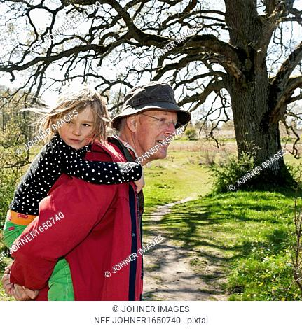 Grandfather carrying granddaughter on shoulders