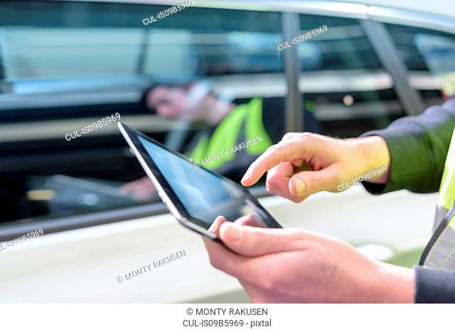 Apprentice car inspector using tablet in car factory, close up