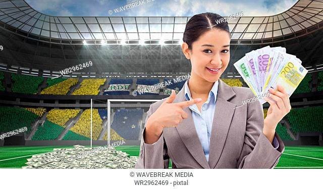 Smiling businesswoman showing money at stadium representing corruption