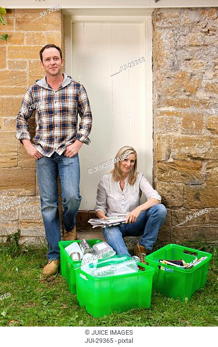 Smiling couple sitting near bins full of recycling materials