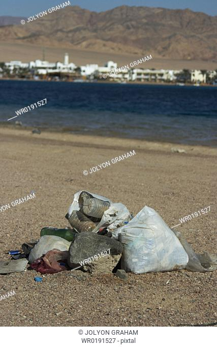 Plastic and glas bottles just left on the beach after a night time party Dahab Egypt