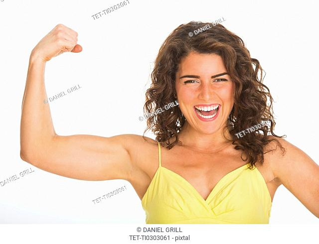 Portrait of young woman showing her biceps, studio shot
