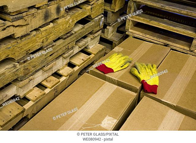 Pair of yellow gloves laying on top of cardboard boxes, which are next to wood pallets