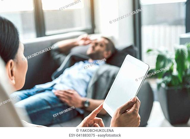 Patient lying on sofa at background. Close up of tablet in female hands