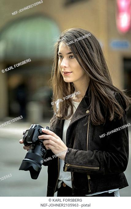 Young woman holding camera