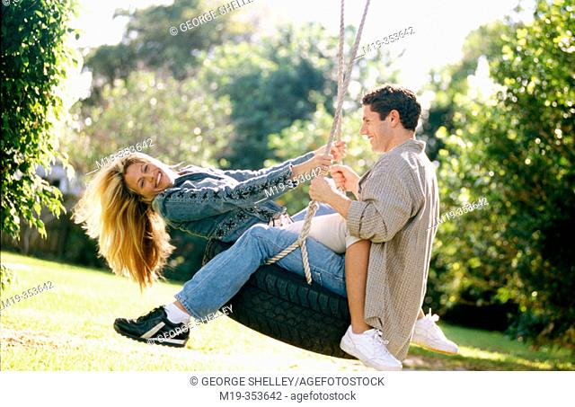 couple on a tire swing