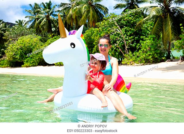 Smiling Portrait Of Mother And Daughter Enjoying Sitting On White Unicorn Float At Beach