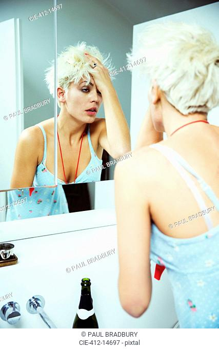 Hungover woman examining herself in mirror