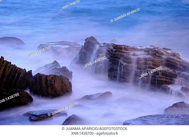 Night photography with long exposure time of sea water breaking on rocks in the Bahia de la Concha in San Sebastian, Spain