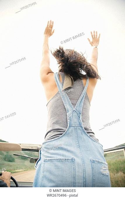 A woman standing with her arms raised in open country, on a road trip