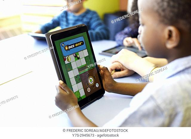 Elementary school children using digital tablets at desk in classroom, Sartrouville,Yvelines , France