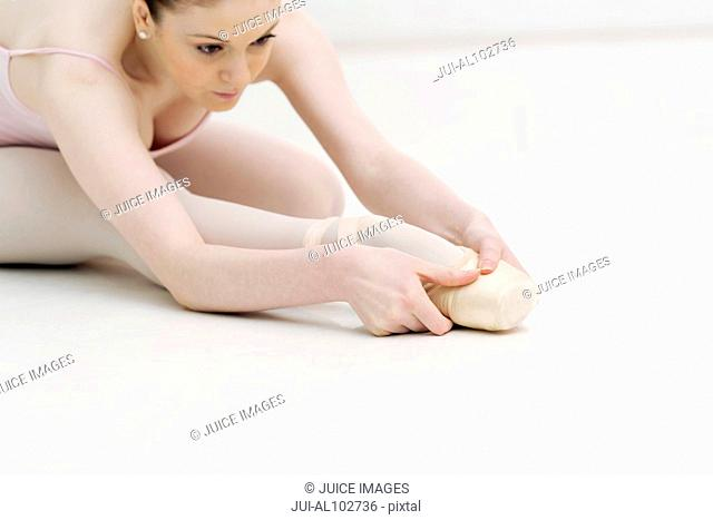 A young ballerina stretching her legs